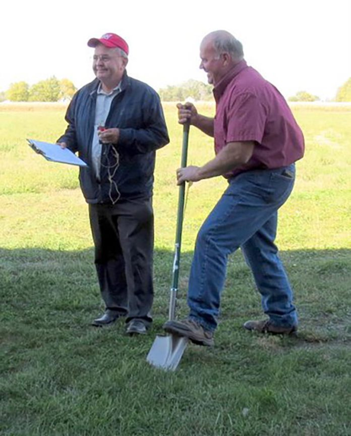 Merrick County Supervisor Jim Helgoth says a few words about his Board's involvement in and support of the process that has come to fruition in the breaking of ground for the new 4-H building at the Merrick County Fairgrounds as Board Chairman Roger Wiegert applies the shovel at the October 18 groundbreaking ceremony.