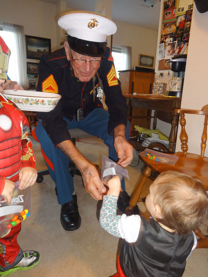 Cottonwood Estates resident Earl Brandes adds candy to a trick-or-treater's collection during the facility's Halloween festivities October 31. Brandes, a retired Marine and World War II veteran, wore his actual Marine dress uniform as his costume, and it still fits! (Photo by Sadie Rima)