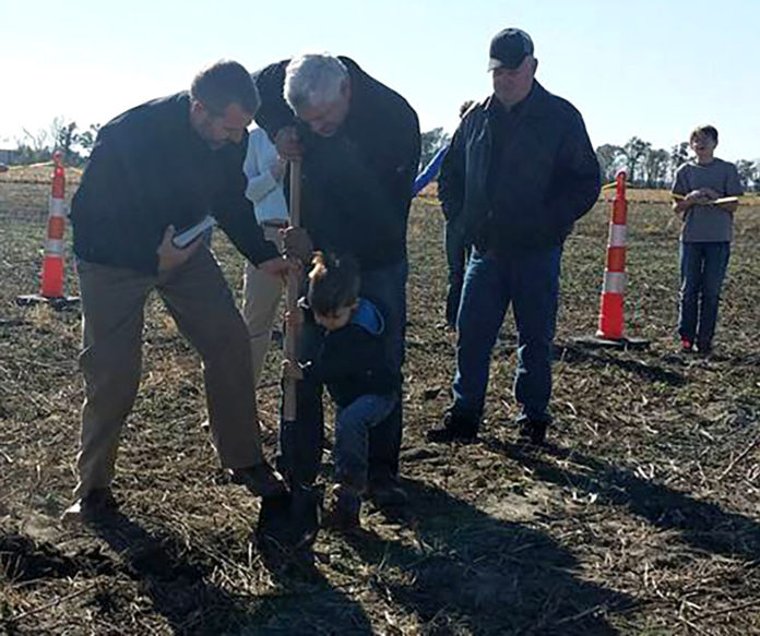 Three-year old Carl McHargue, assisted by his grandfather Mark and Heartland E Free pastor Zeke Pipher (left), drives a shovel in the dirt to mark the breaking of ground for the church's new multi-phase construction project as Central City's Wendell Faeh looks on.