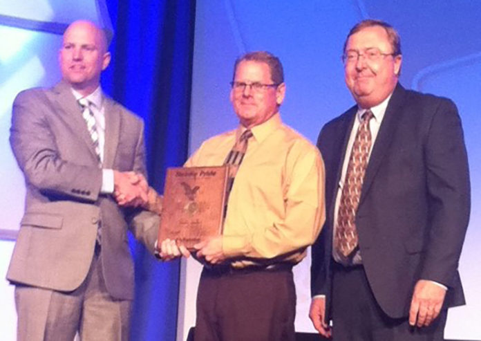 Kent Malm (center) of Central City's Herk's Welding, Inc. accepts a Reinke Gold Pride award from Reinke Manufacturing president Chris Roth at Reinke's Annual Sales Meeting in Dallas, Texas, on Saturday. Flanking Malm on the right is Dan Glenn, Reinke territory manager for the East Central region.
