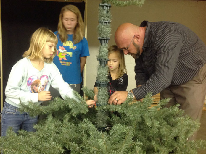 Sarah Musil, Kynzi Muller, Chloe Jefferson, and Chris Lovejoy put up a Christmas tree for the stage set during the cast and crew supper