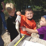 Children attending the 2015 Family Wilderness Event show off a fish for the judges to weigh and measure. A fishing contest will also be part of the activities for the event on September 23 at Bader Park.